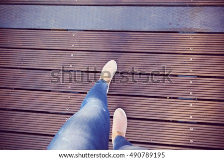 Women's beautiful legs walking through modern wooden bridge
