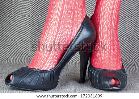 women's black leather shoes with red delicate tights - stock photo