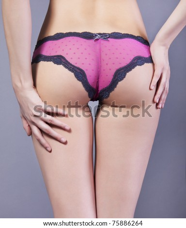 Women's Booty in pink lace panties on a gray background of the body part - stock photo