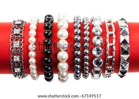Women's bracelets on the red hat on a white background - stock photo