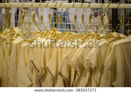 women's cloths on hangers in a retail shop - stock photo