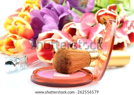 Women's cosmetics for Makeover: blush and lip gloss on a background of colorful flowers tulips - stock photo