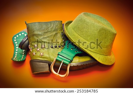 Women's cowboy outfit: leather boots rivets, hat, leather belt with buckle - stock photo