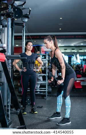 Women's day in the gym. Two women athletes doing exercise at the gym. - stock photo