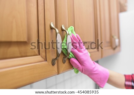 Women's gloved hand wipe the dust from the locker door. Close-up. - stock photo