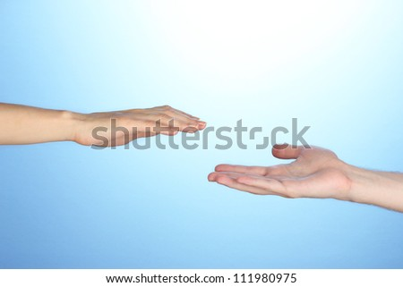 Women's hand goes to the man's hand on blue background - stock photo