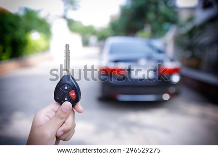 women's hand presses on the remote control car alarm systems - stock photo