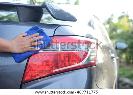 Women's hand with microfiber cloth cleaning her car.