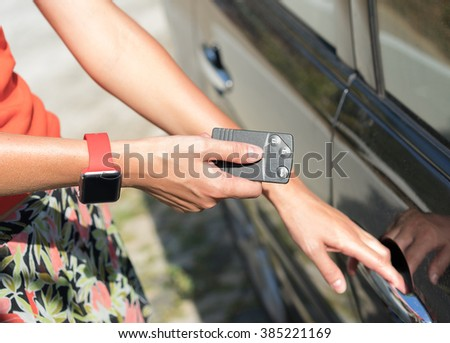 women's hand with smart watch presses on the remote control car alarm systems - stock photo