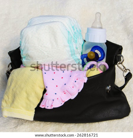 Women's handbag with items to care for the child - stock photo