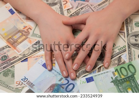 women's hands are covered banknotes of the Euro and the dollar - stock photo