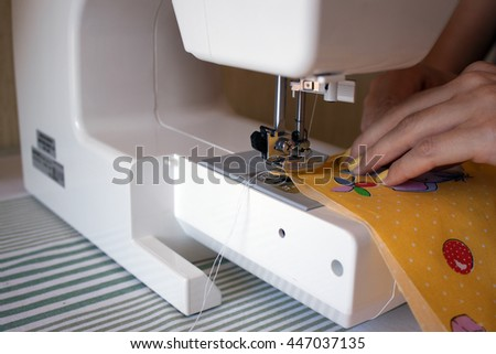 Women's hands behind her sewing/sewing machine