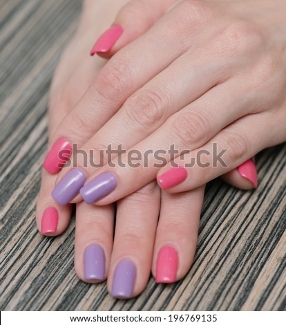 Women's hands with a colored nail polish - stock photo