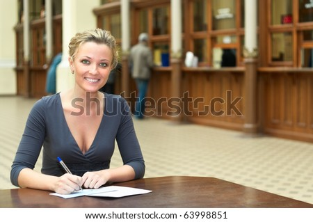 Women's hands with a handle filling the form on the desk in the office