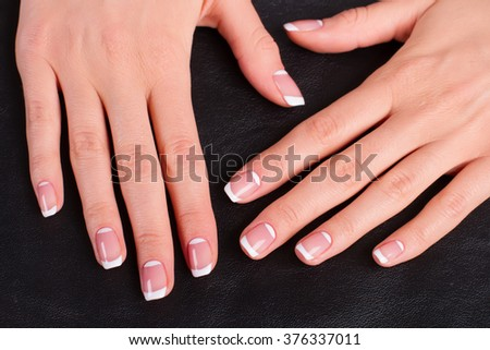Women's hands with a stylish manicure. Female hands on a black leather background.