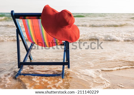 Women's hat on a beach chair on the beach - stock photo