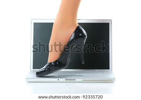 Women's legs and the laptop. Isolated on white. - stock photo