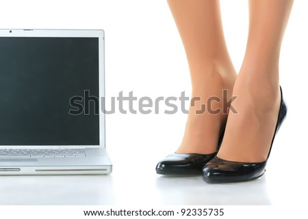 Women's legs and the laptop. Isolated on white.
