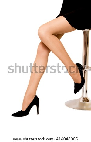 Women's legs in pantyhose and high heels. Neutral color. Woman on a bar stool. Classic shoes. - stock photo