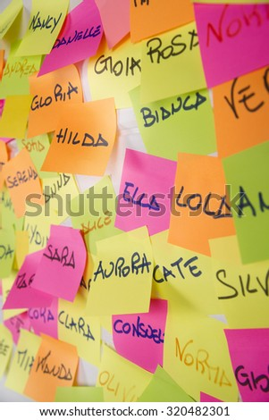 Women's names written on small pieces of paper of different colors - stock photo