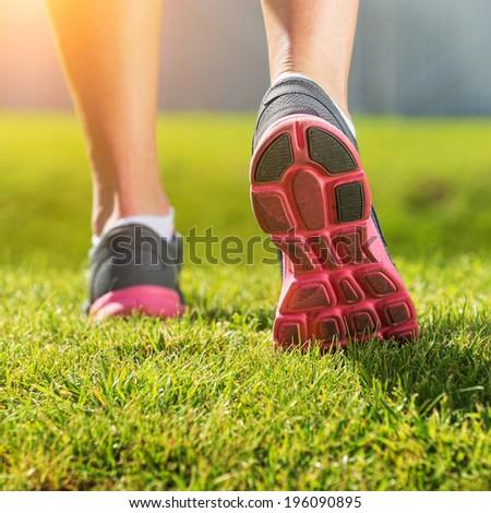 Women's running legs, pink-gray sports shoe detail - stock photo