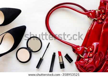 Women's set of fashion accessories on wooden background: shoes, handbag and cosmetics - stock photo