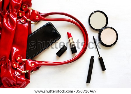 Women's set of fashion accessories on wooden background: shoes, handbag, cell phone and cosmetics - stock photo