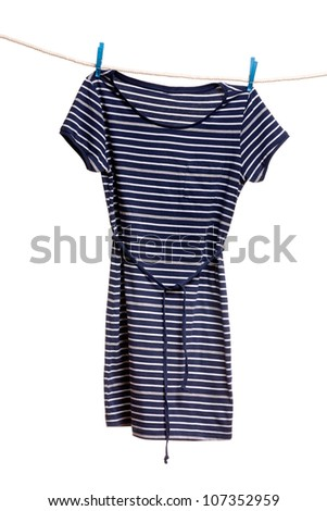 Women's striped dress hanging on a rope with clothespins. Isolate on white. - stock photo