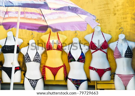 Women's swimsuits on mannequins for sale at a seaside shop - stock photo
