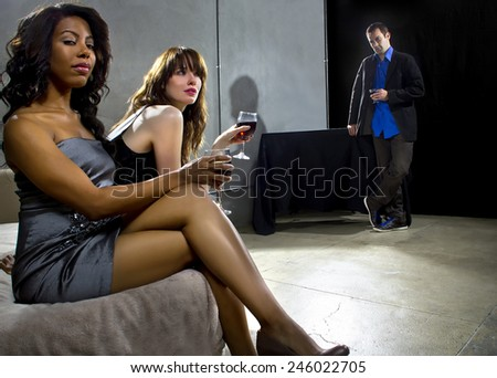 women seducing a man at a bar or nightclub - stock photo