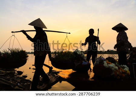 Women selling flowers on a boat in the early morning  - stock photo