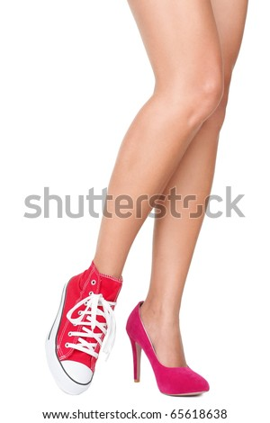 Women shoes. Red high heels and sports shoes / sneakers. Closeup of woman legs and feet wearing two different shoes. Isolated on white background. - stock photo