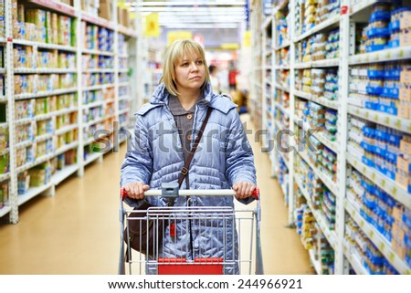Women shopping in supermarket with cart - stock photo