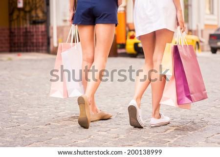 Women shopping. Rear view of two beautiful young women carrying shopping bags while walking along the street - stock photo
