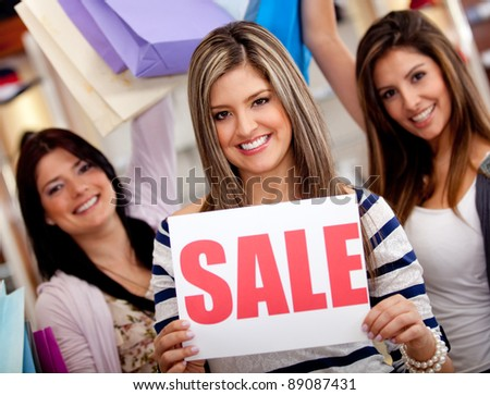 Women shopping while saleswoman displays a sale sign