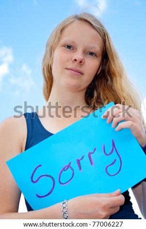 Women show shield: Sorry - stock photo