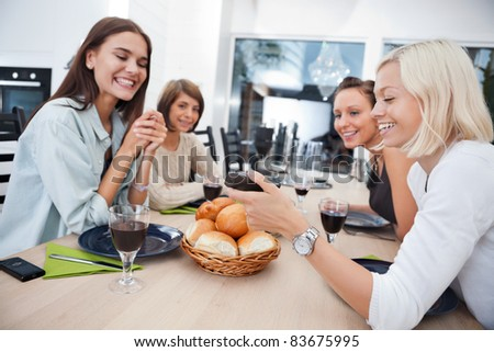 Women showing something to her friends on mobile phone at dining table - Shallow Depth of field critical focus on phone - stock photo