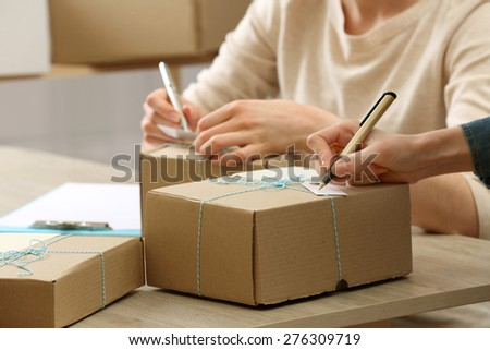 Women signs parcels in post office - stock photo