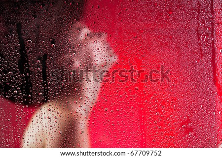 Women silhouette behind wet glass