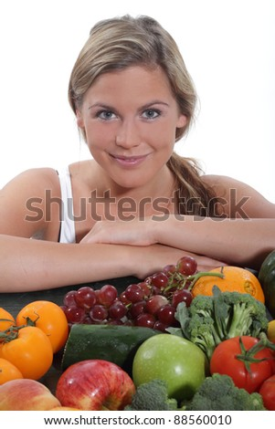 Women sits near a table spread with fresh vegetables and fruit