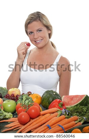 Women sits near a table spread with fresh vegetables and fruit - stock photo