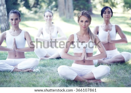 Women sitting in lotus position during yoga training at park - stock photo