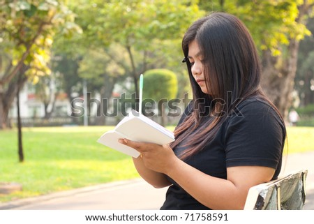 Women sitting in the park and is writing a notebook in it.