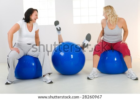 Women sitting on fitness balls. One of them slump from the ball. Two women laughing. Front view. - stock photo