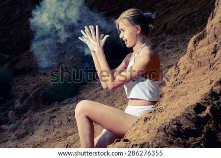 Women sitting on sand with cloud of white dust fly around. - stock photo