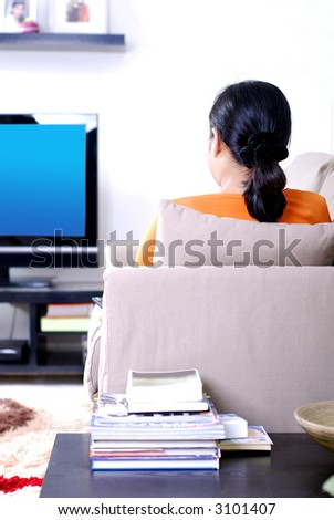 Women sitting on sofa watching television