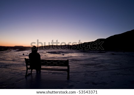 women sitting on the bench at night near Geyser in Iceland - stock photo