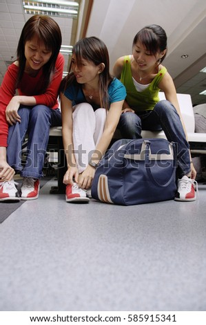 Women sitting, putting on bowling shoes