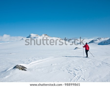Women skiing alone between some rocks at easter heading towards twin summits in the norwegian mountains - stock photo