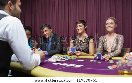 Women smiling at dealer in poker game - stock photo